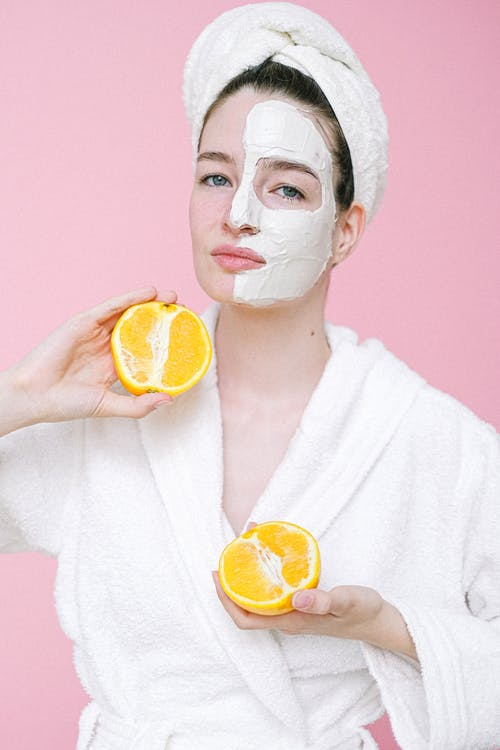 Content woman with facial mask on half of face