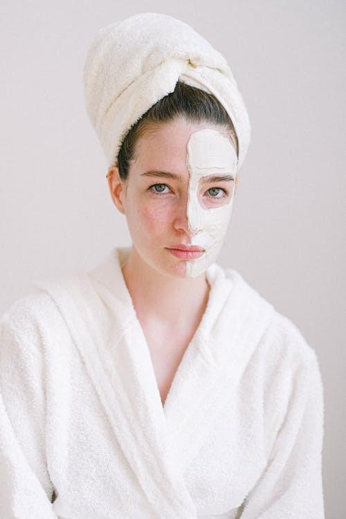 Young attractive female in white bathrobe and towel on head standing in spa salon with rejuvenating facial mask on half face and looking at camera