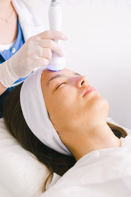 Professional female beautician in gloves and robe using ultrasound apparatus to clean female customer face lying with eyes closed in spa center