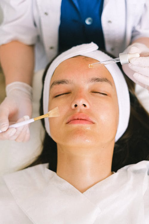 Top view skilled female cosmetologist in uniform and gloves applying essential oil on young woman face skin while working in contemporary spa center