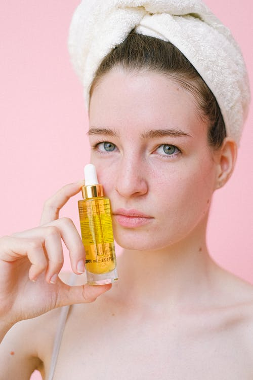 Crop young female without makeup and with hair wrapped in towel showing cosmetic product holding bottle near pretty face and looking at camera