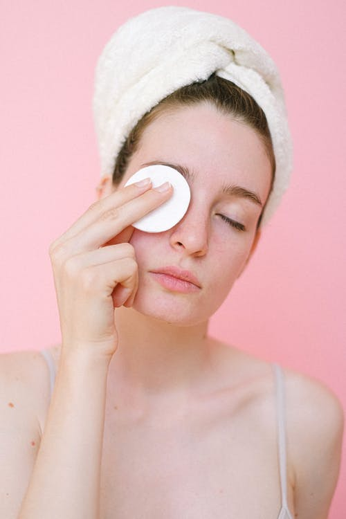 Woman removing eye makeup with cotton pad