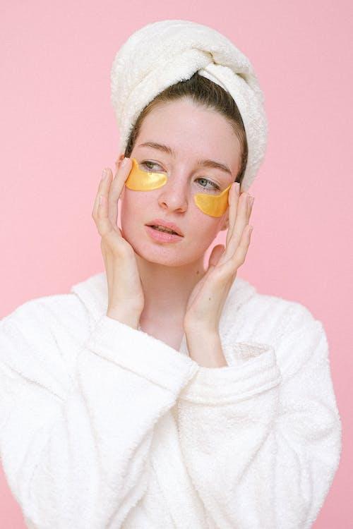Woman applying eye patches in bathroom
