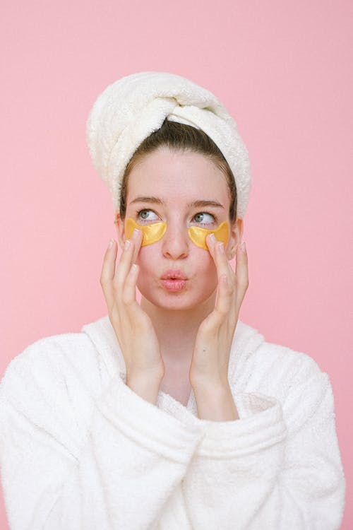 Attractive young female wearing white bathrobe and towel on head applying eye patches on face and pouting lips while looking away against pink background