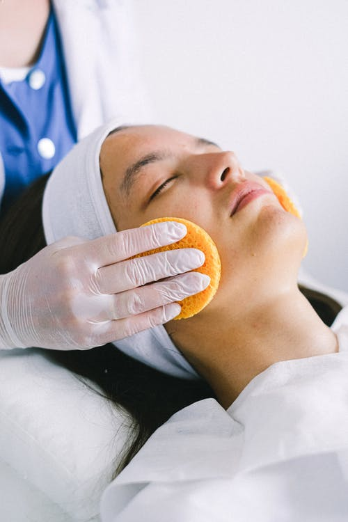 Female beautician in medical robe and gloves using yellow sponges to clean female customer face lying with eyes closed in spa