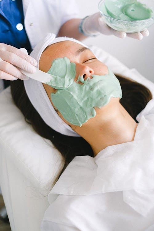 High angle professional female beautician applying moisturizing facial mask on serene female customer face skin in light contemporary beauty clinic