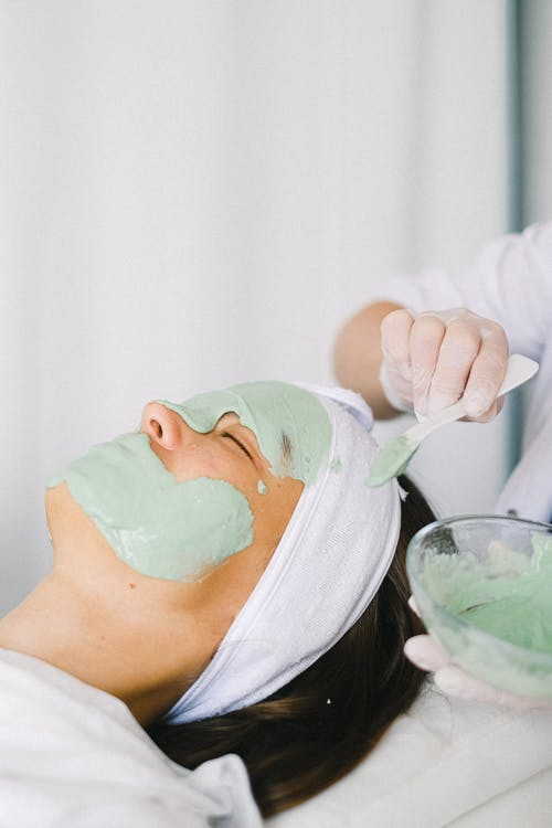 Cosmetician applying facial mask on client face