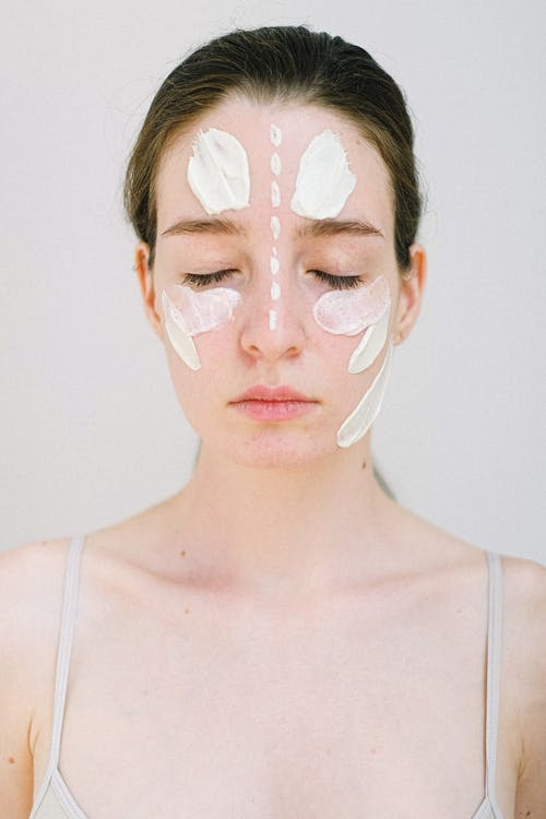 Young female model with perfect skin applying cosmetic cream on face while standing with closed eyes on white background