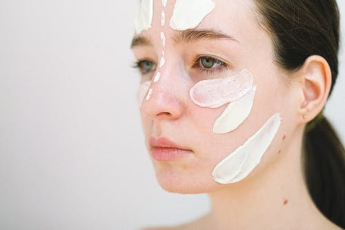 Side view of crop female model spreading white cream on face during skincare procedure on white background
