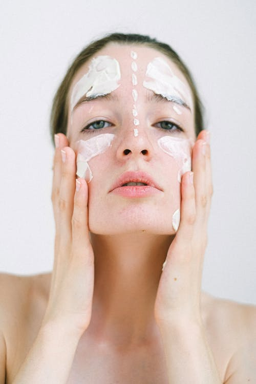 Young lady putting on cheeks cosmetic mask