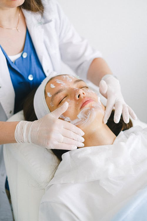 From above of crop faceless cosmetician applying facial mask on customer face during cosmetic procedure in modern spa salon
