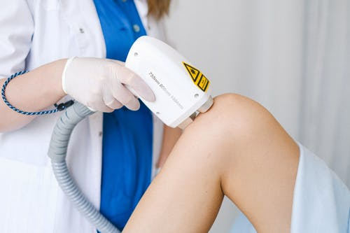 Crop unrecognizable cosmetologist in medical uniform using probe while doing low level laser therapy to calm patient in beauty salon