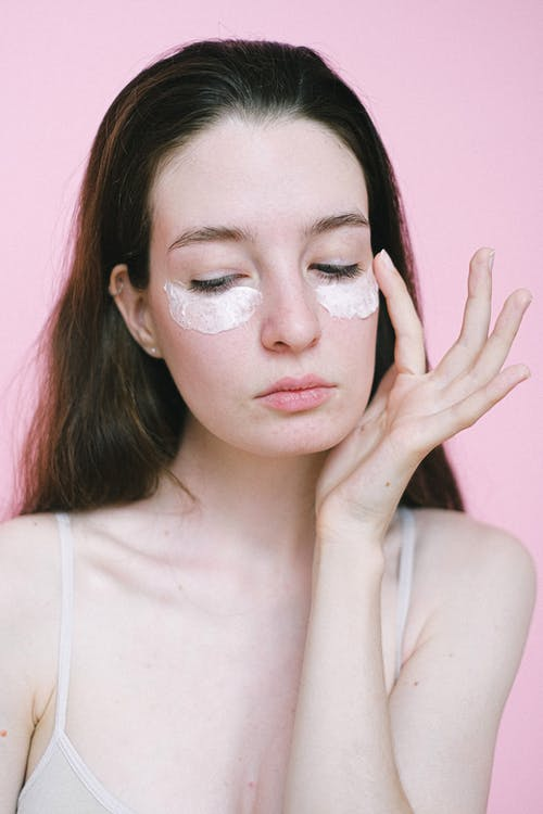 Young woman with dark hair in top applying moisturizing facial cream under eyes against pink background in studio