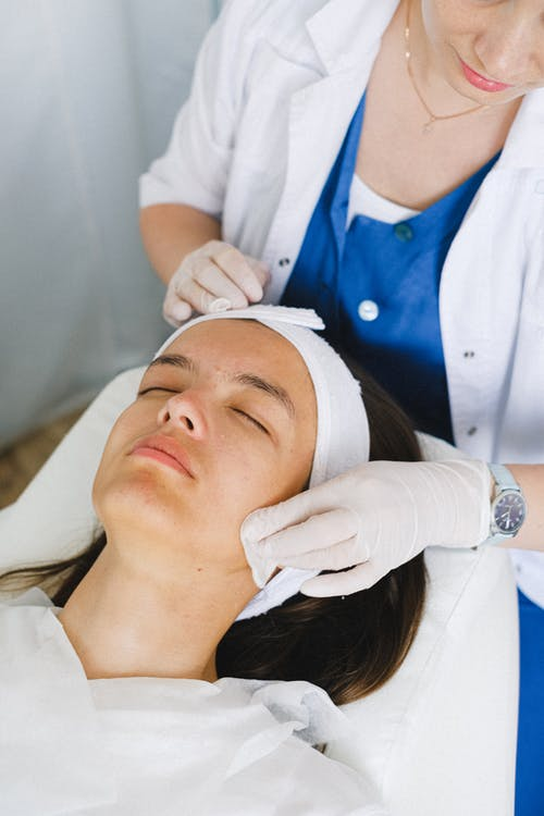 From above of crop anonymous cosmetologist in medical uniform cleaning face before facial procedure in beauty clinic
