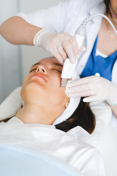 Crop unrecognizable female cosmetologist in medical uniform and gloves doing ultrasonic face cleaning procedure in beauty clinic