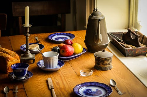 Blue and White Ceramic Plate Next to Apple Fruit and Brown Tea Pot