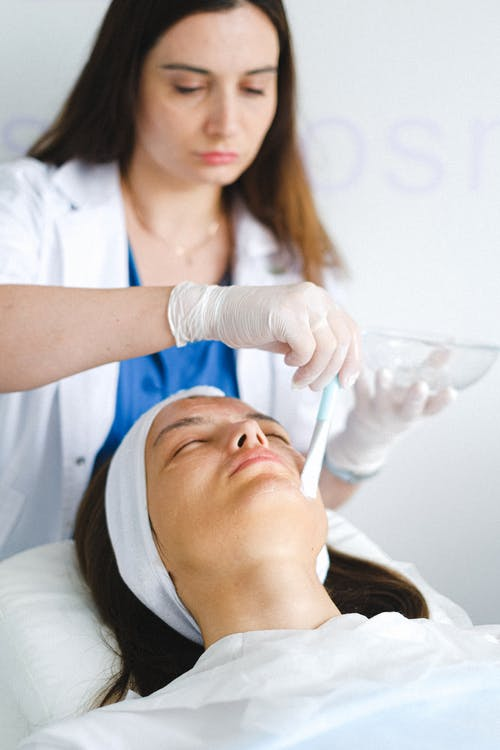 Concentrated female cosmetologist in medical uniform and gloves using brush to apply cosmetic mask on face of client with closed eyes