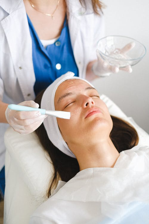 From above of crop cosmetician putting moisturizing lotion on face during beauty procedure in salon