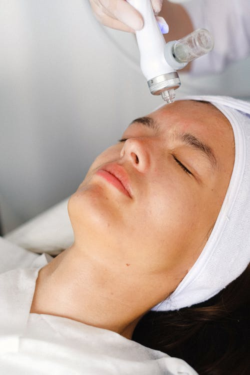 High angle of crop professional cosmetician doing face skin care therapy with laser tool