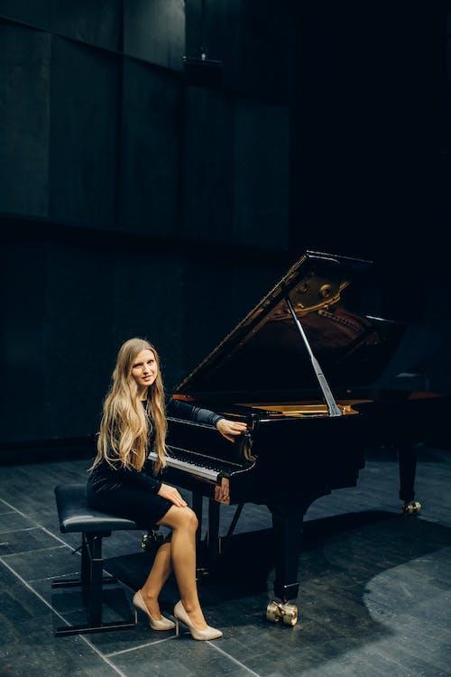 Blonde Woman Playing Grand Piano