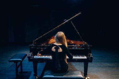 Woman in Black Long Sleeve Shirt Playing Grand Piano