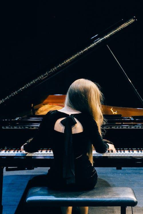 Woman in Black Long Sleeve Shirt Standing Beside Grand Piano