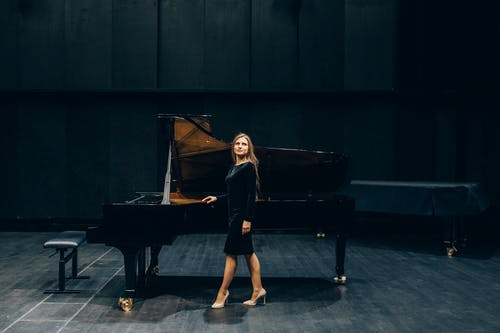 Woman in Black Dress Playing Piano