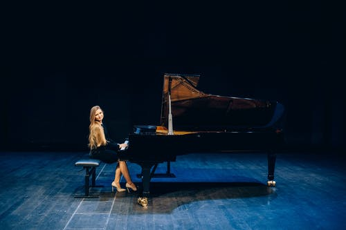 Woman in Black Dress Playing Grand Piano