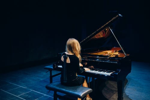 Woman in Black Long Sleeve Shirt Playing Piano