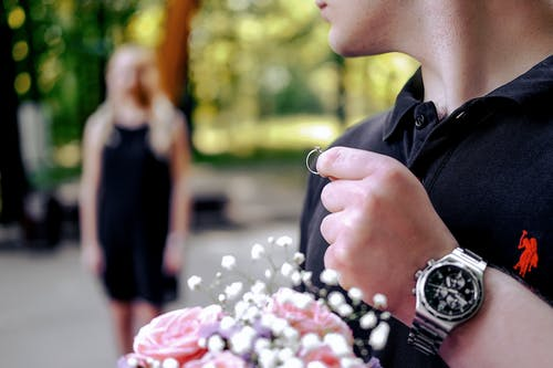Soft focus of young male in casual clothing holding wedding ring and bouquet of flowers while going to make proposal to woman in garden on blurred background