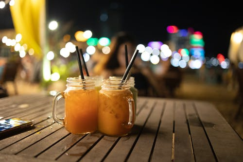 Glass jars with black straws and delicious orange cocktails placed on wooden table on blurred background with bright lights