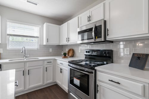 White Wooden Kitchen Cabinet and Black and Silver Gas Range Oven
