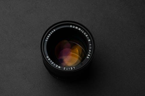 Modern photo camera lens on black table