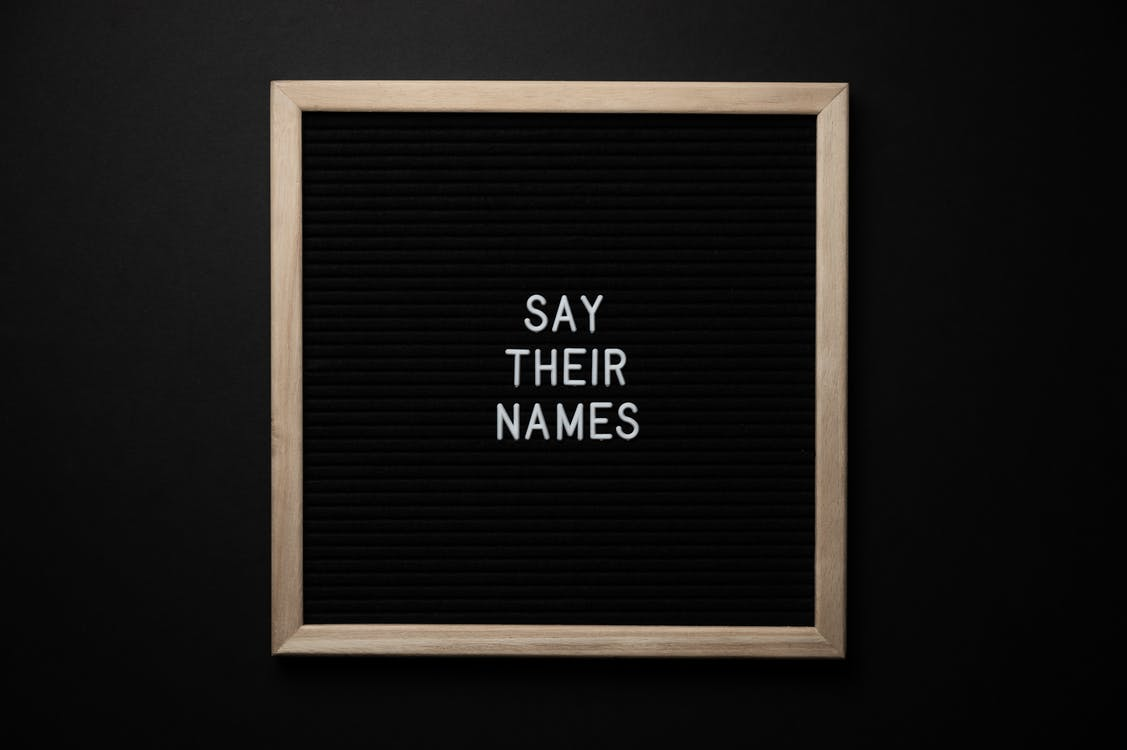 Top view composition of black framed photo with white text Say Their Names placed on black background
