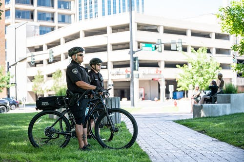 Side view full length serious bicycle patrol policemen in uniforms and helmets standing on city lawn