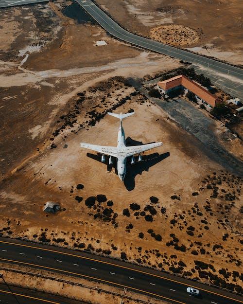 Biały Samolot Lecący Nad Brązowym Polem
