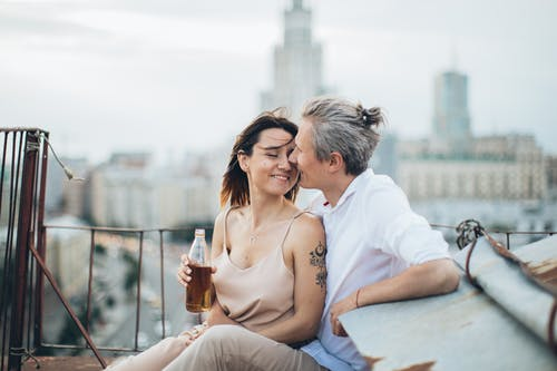 Cheerful couple in stylish clothes caressing each other while resting on rooftop of city