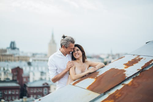 Smiling couple hugging on city roof