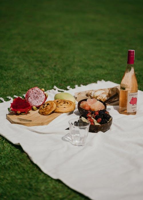Sliced Bread on White Ceramic Plate Beside Wine Bottle and Bread on White Table