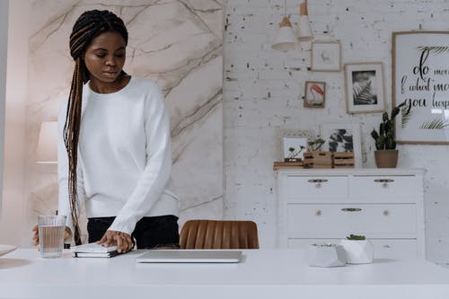Woman in White Long Sleeve Shirt Standing Beside White Table