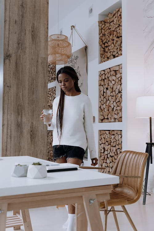 Woman in White Long Sleeve Shirt and Black Pants Standing Beside White Table