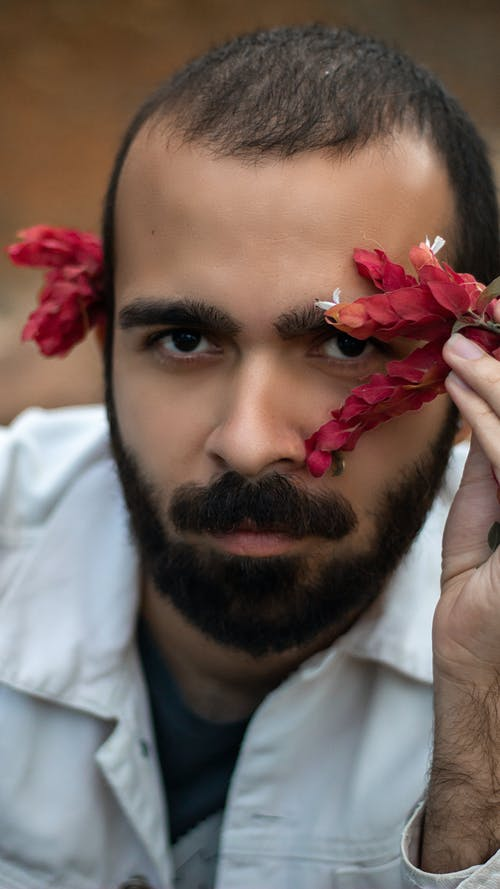 Man in White Dress Shirt With Red Flower on His Head