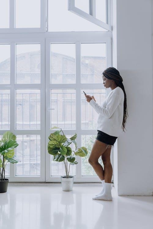 Foto profissional grátis de afro-americano, aparelho eletrônico, celular