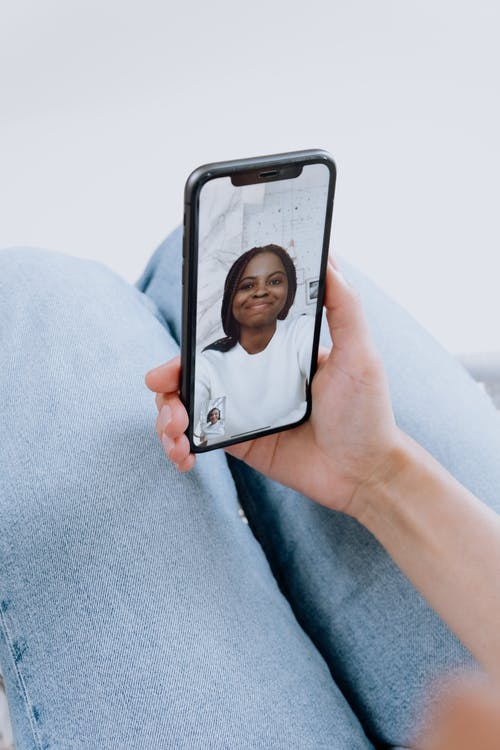 Person Holding Iphone With Black Case