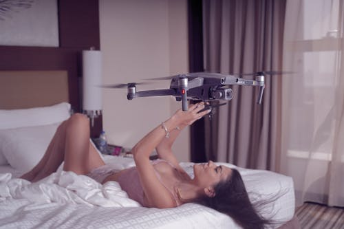 Woman Lying on Bed Holding Black and Silver Drone