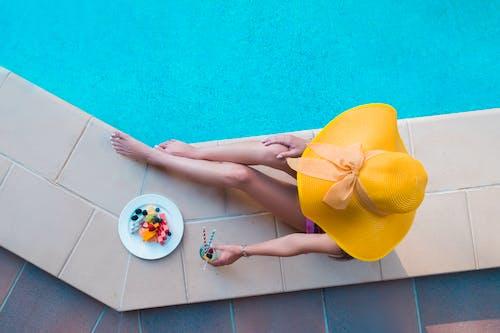 Woman in Yellow Dress Standing on Blue Floor Tiles