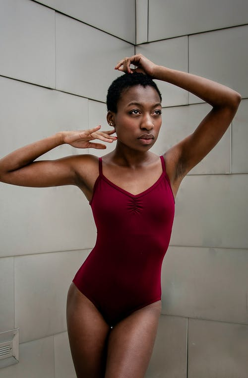 Fit young black ballerina standing near tiled wall