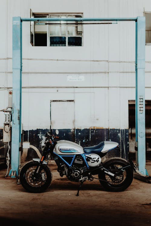 Blue and White Naked Motorcycle Parked Beside White Wall