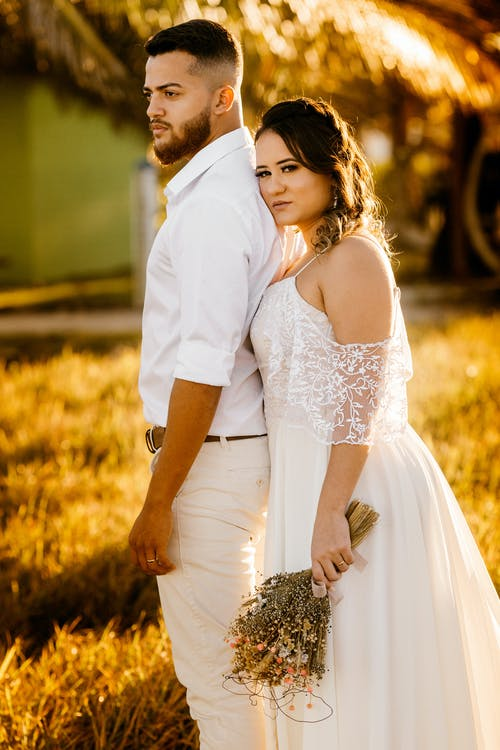 Dreamy young newlywed couple standing together on grassy meadow in countryside