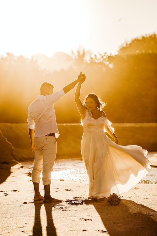 Cheerful newlywed couple dancing on sandy coast on sunny day